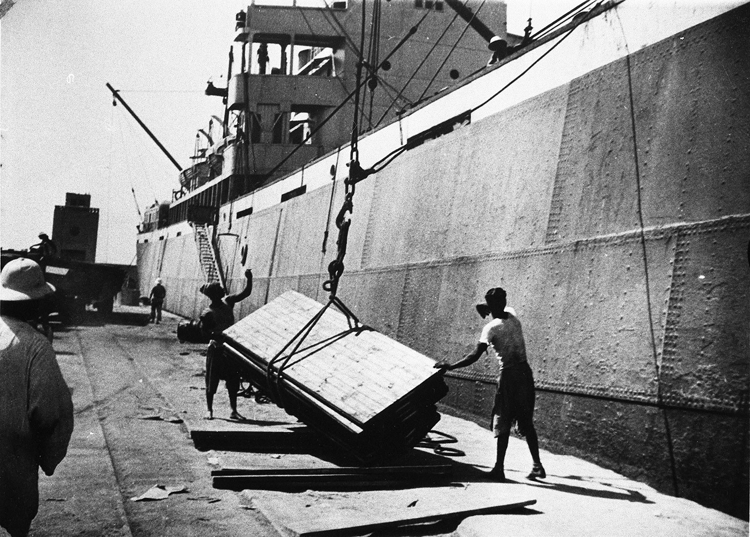 Black and white photo of Puutalo Oy panels being discharged at a harbour.