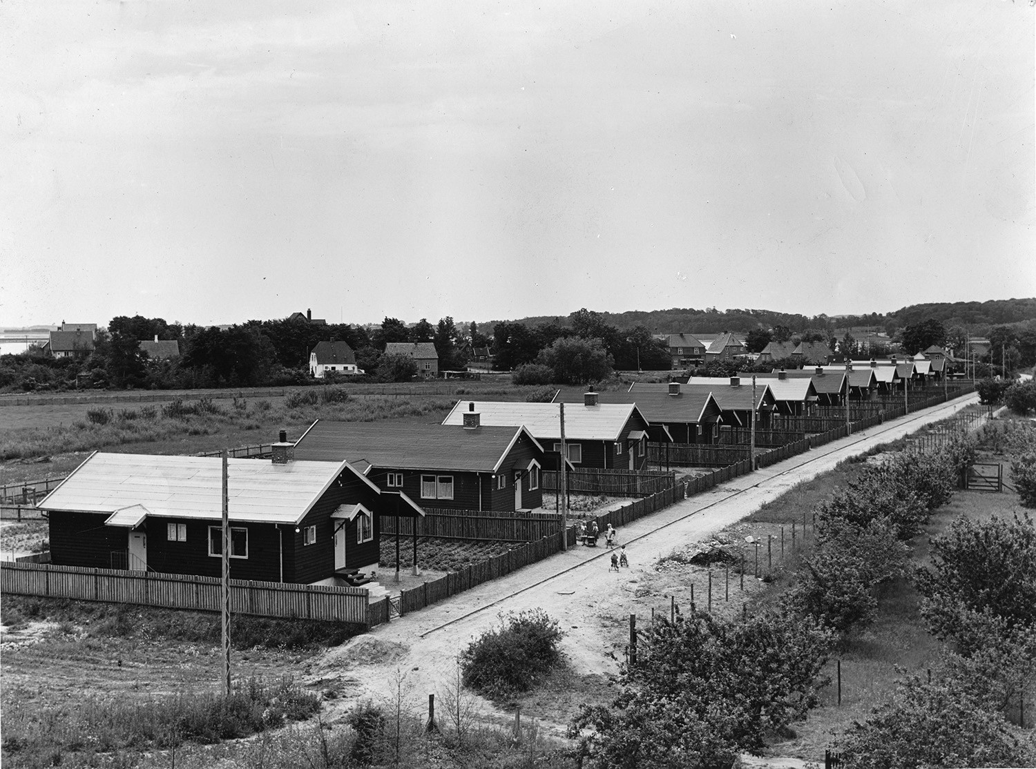 A black and white photo of a street with Puutalo Oy's detached houses on adjacent fenced plots.