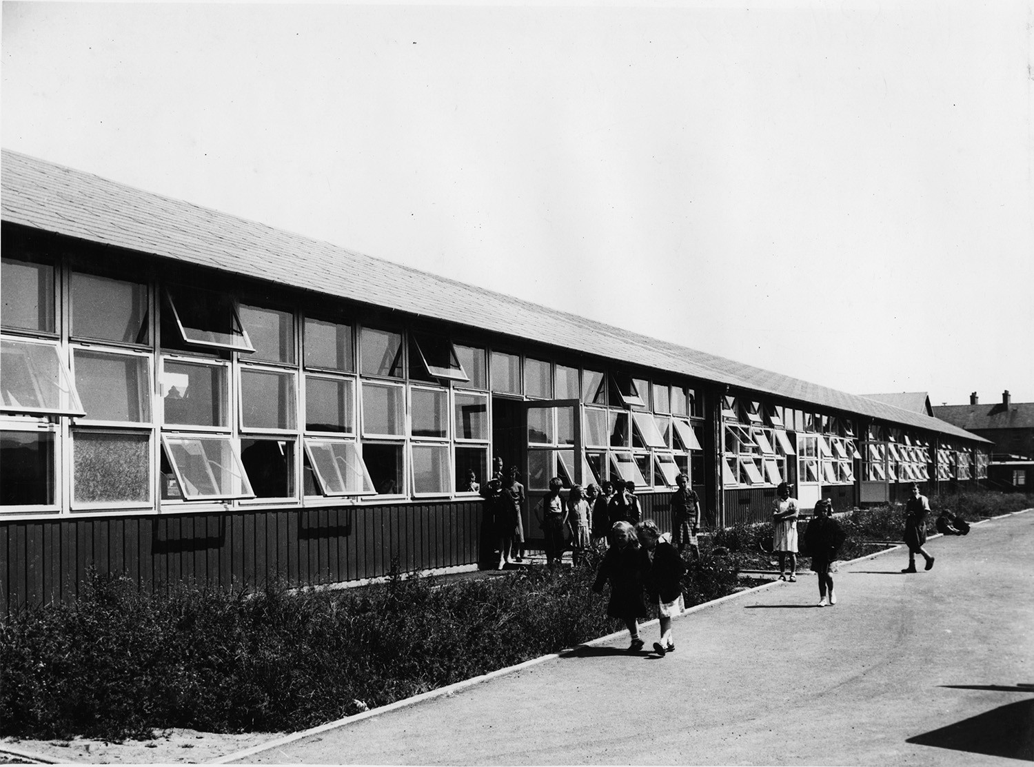 An old black and white photo of a Puutalo wooden school. The school's wall has many windows right next to each other and some of them are open.