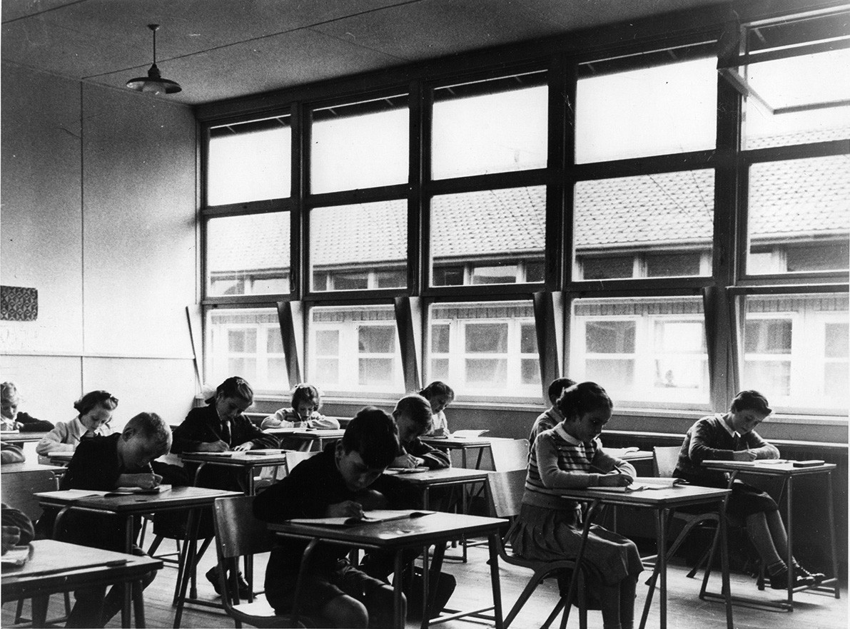 An old black and white picture of a classroom, children writing at their desks, a wall of windows in the background.
