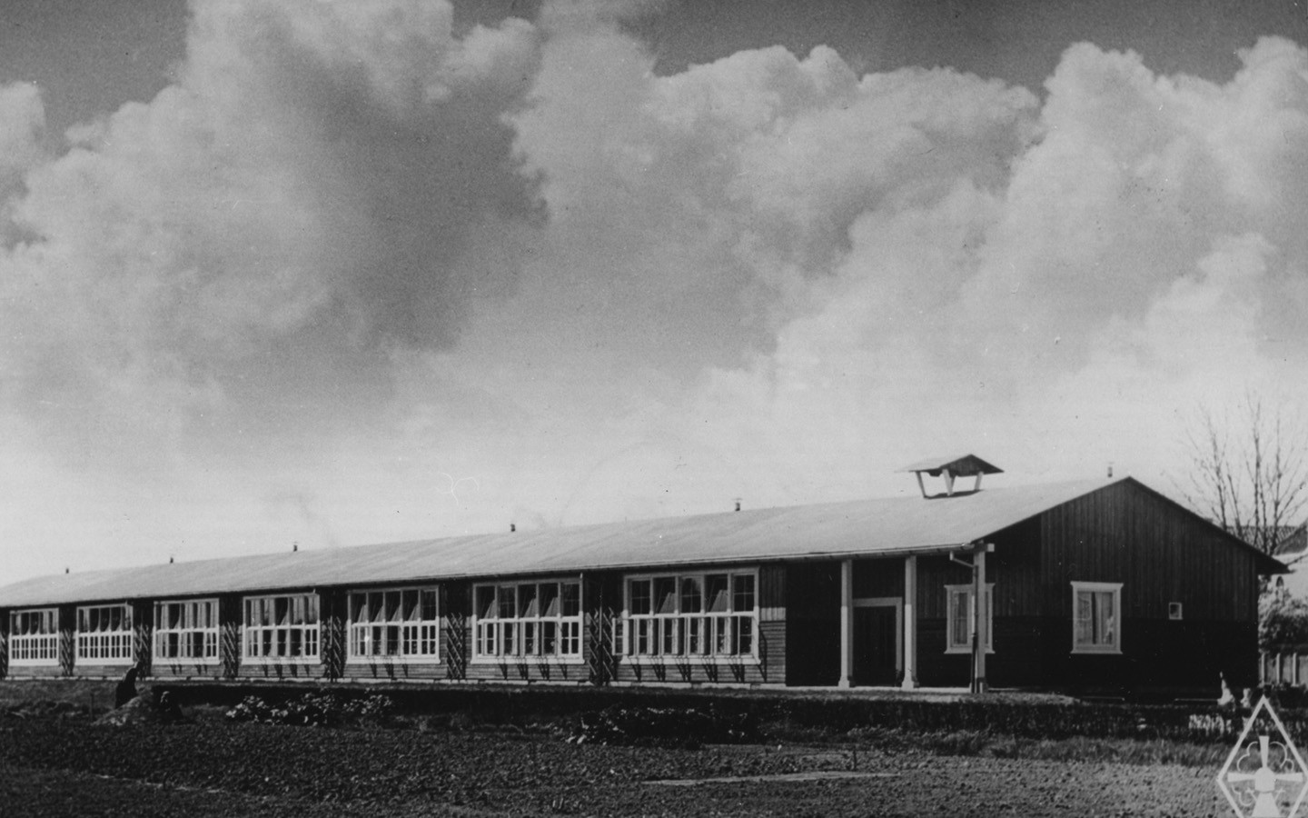 Black and white picture of a long one-storey school building with a pitched roof. Dark-painted wooden facades, white window frames.