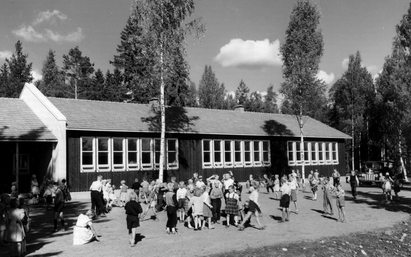 An old black and white picture of a wooden school where there are children playing in the yard.