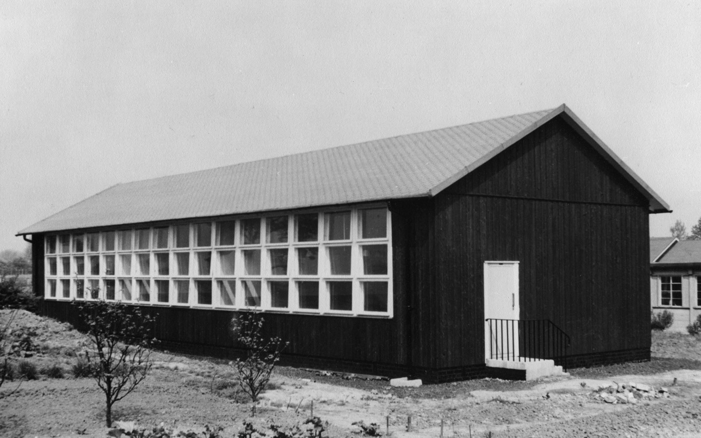 An old black and white photo of a wooden Puutalo school. On the wall there are 3 rows of windows with 16 windows in each.