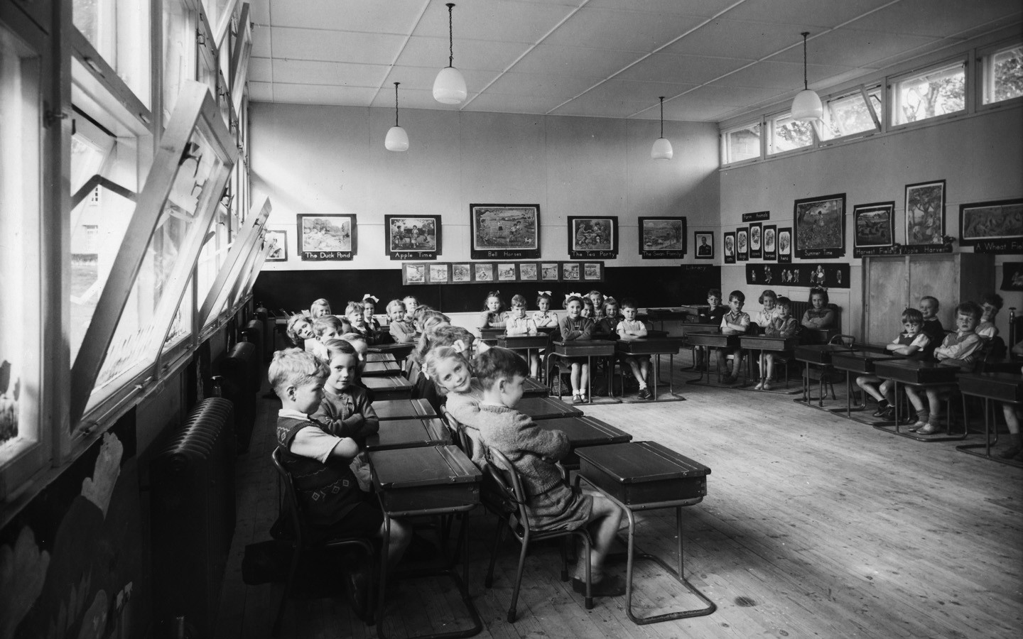 An old black and white photo of a class room where there are children sitting at their desks.