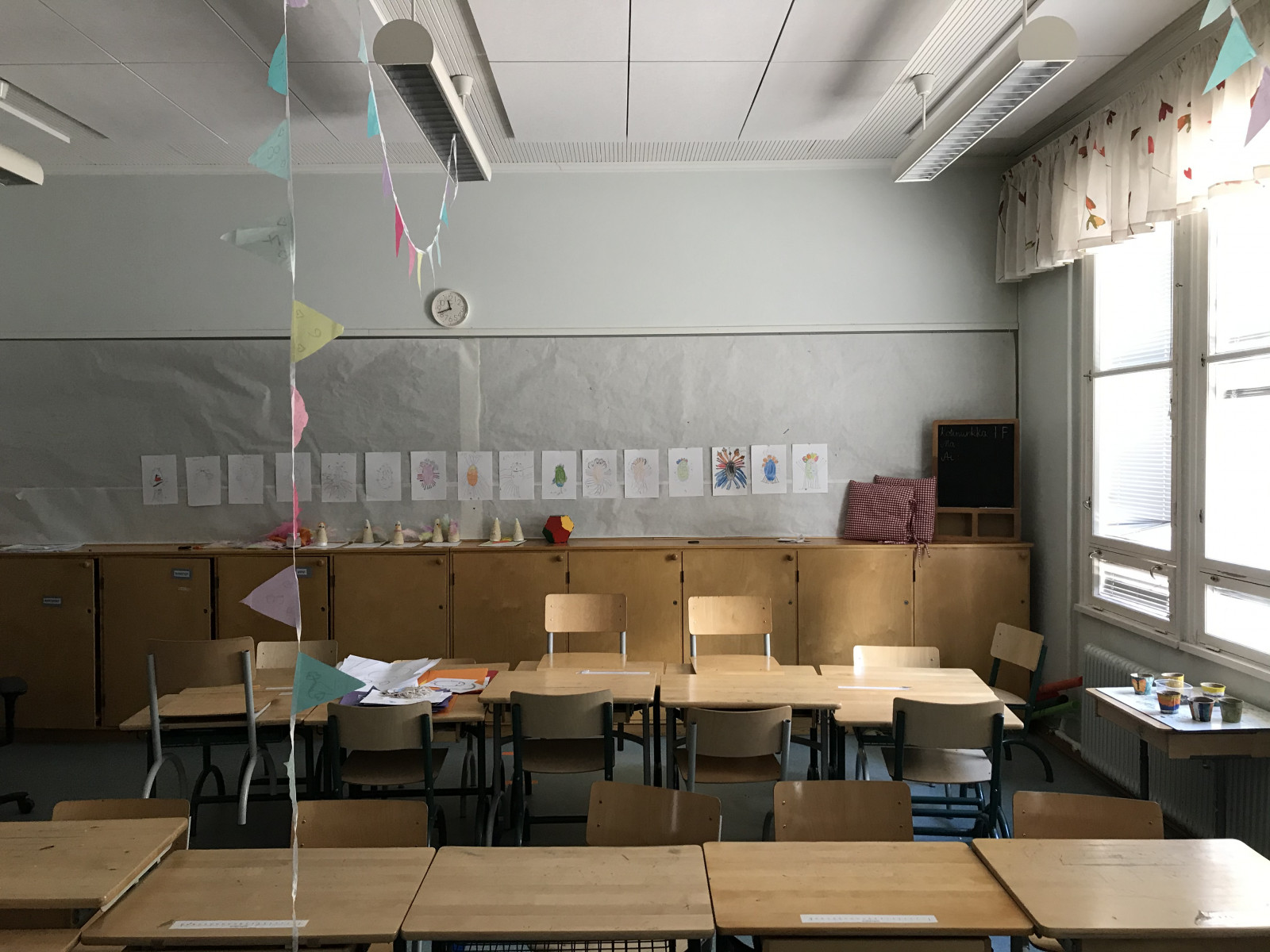 An empty classroom. There are decorations like streamers and pictures around.