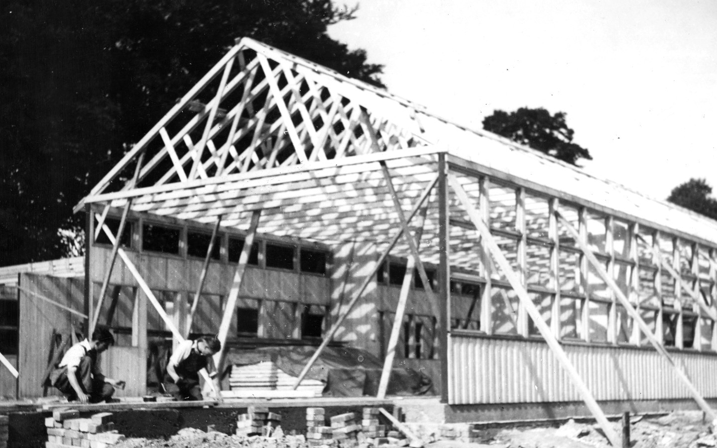An old black and white picture of a Puutalo school under construction. The frame and roof crest are up.
