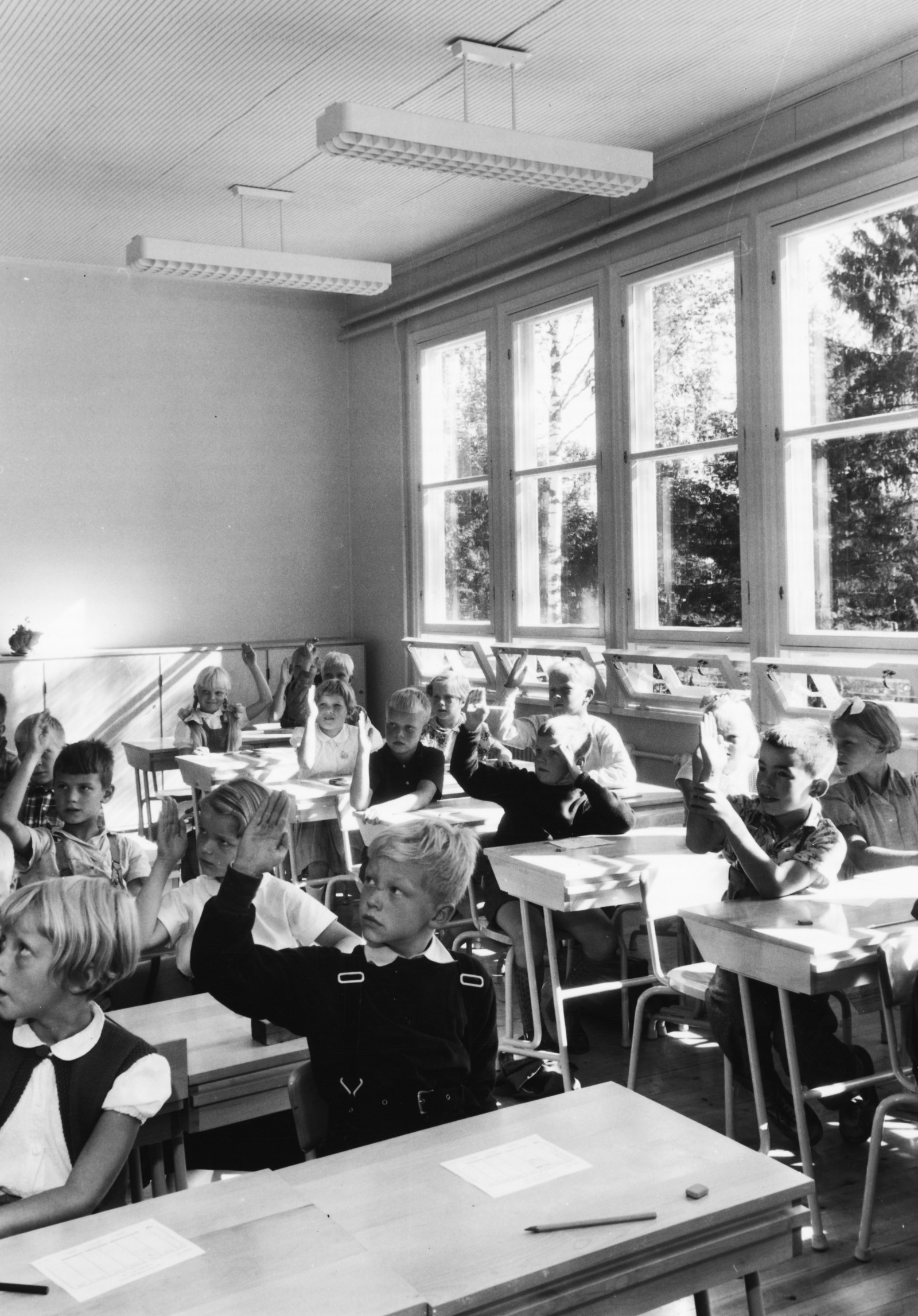 Black and white photo of Puutalo school classroom, where a class is in session. The pupils are raising their hands.
