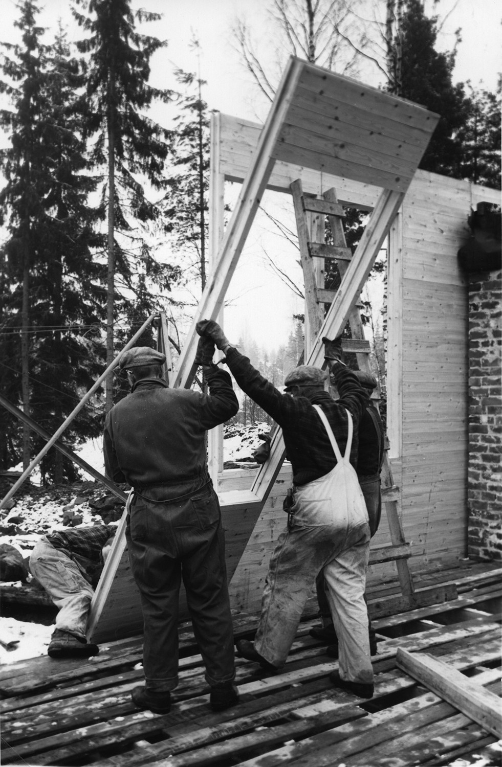 A black and white photo of three workers putting up a wall of a wooden Puutalo school.