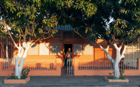Orange house with big trees in front, white shutters. Evening light, man standing at the doorway.