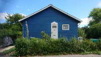 Gable of a small blue wooden house.