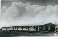 Schools delivered to the Netherlands featured an elongated single-story volume covered by a gently sloping roof and large windows to the south.